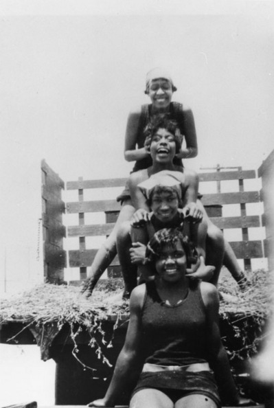 Caption reads: ''Women in bathing suits stack on top of each other in the back of a truck on a hayride to Manhattan Beach (Bruce's Beach). Top to bottom, Susie Thorton, Grace Williams, Mary Mingleton, Grace Harris,'' ca. 1925   Shades of L.A. Collection, Los Angeles Public Library
