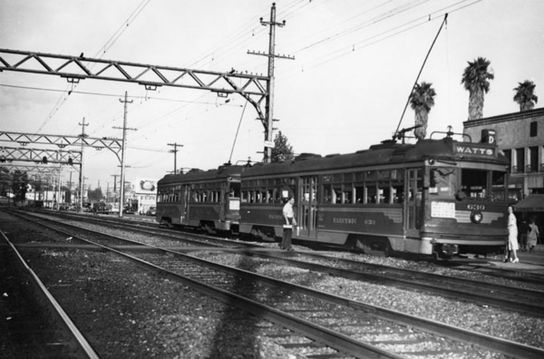 A man waiting to board a waiting Pacific Electric car at the Watts station circa 1940s | Security Pacific National Bank Collection, Los Angeles Public Library