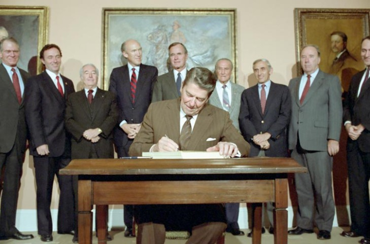 11/6/1986 President Reagan in the Roosevelt Room signing S. 1200 Immigration Reform and Control Act of 1986 with Dan Lungren Strom Thurmond George Bush Romano Mazzoli and Alan Simpson looking on