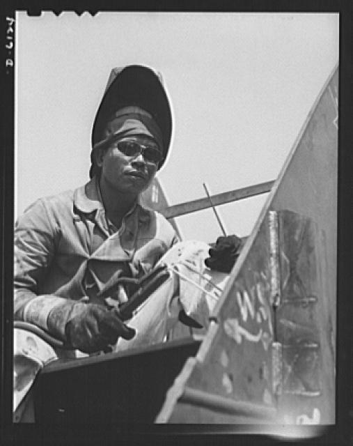 """Construction of the liberty ship ""Booker T. Washington."" Jack Dover, Filipino welder assigned to work on the ""Booker T. Washington,"" first liberty ship named for a Negro, is one of the workers of many racial groups who rushed to complete the vessel which bears the name of the noted Negro educator""; Photograph by Alfred E. Palmer, September 1942, Farm Security Administration, Prints and Photographs Division, Library of Congress"